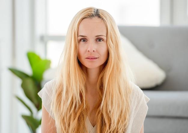 Портрет довольно привлекательной блондинки без макияжа дома