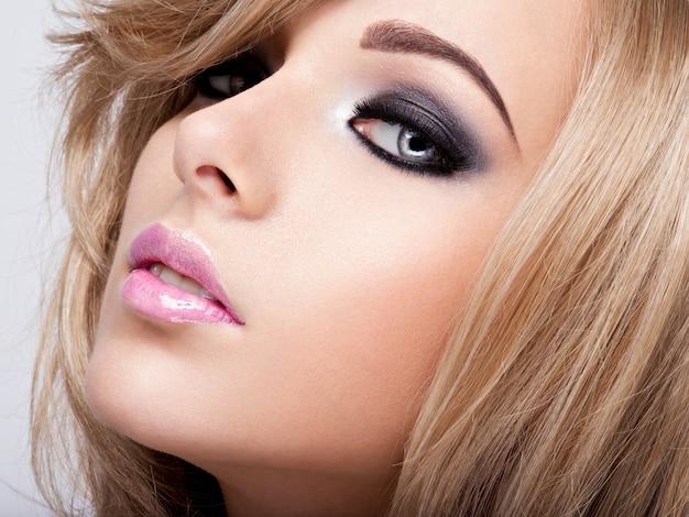밝은 화장으로 꽤 매력적인 젊은 여자의 초상화. 아름다운 갈색 머리.