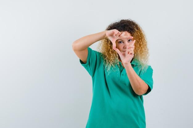 Портрет симпатичной блондинки, делающей треугольный жест в зеленой футболке-поло и смотрящей сфокусированным видом спереди