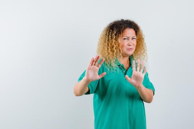 Портрет красивой блондинки, показывающей жест отказа в зеленой футболке-поло и выглядящей с отвращением, вид спереди