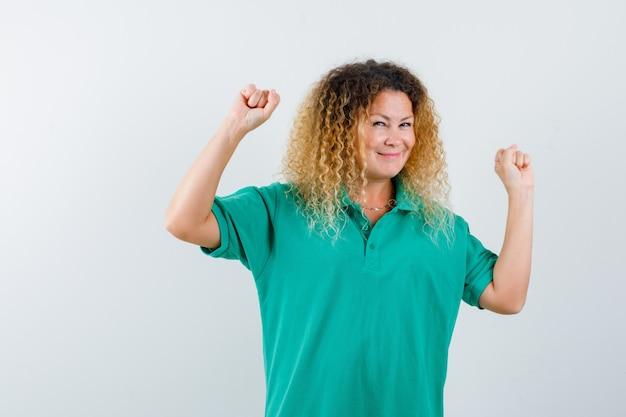 緑のポロtシャツで勝者のジェスチャーを示し、至福の正面図を見てかわいい金髪の女性の肖像画
