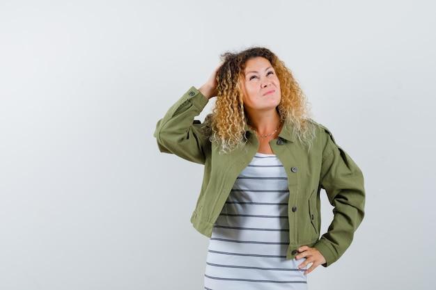 緑のジャケットで頭を掻き、物思いにふける正面図を探しているかなり金髪の女性の肖像画