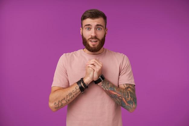 Портрет симпатичного голубоглазого бородатого брюнет с татуировками, жалко поднимающего сложенные руки, в бежевой футболке и модных аксессуарах, позирующий на фиолетовом