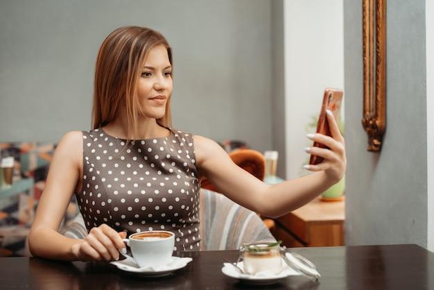 Портрет красивой шатенки, делающей селфи на мобильном телефоне за столом в ресторане