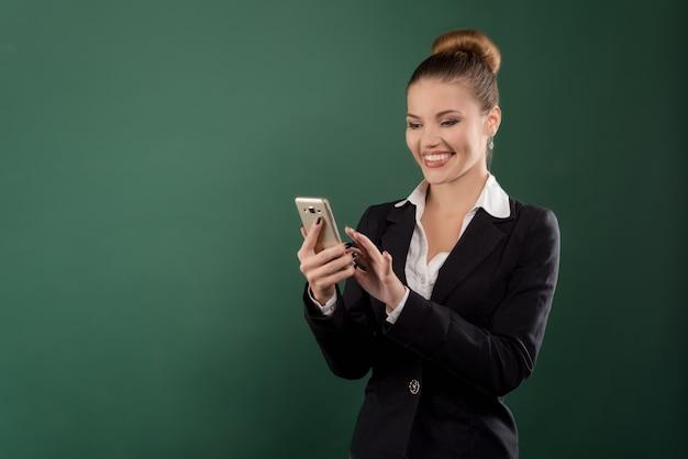 Портрет красивой деловой шатенки, читающей что-то на своем мобильном телефоне на зеленом фоне