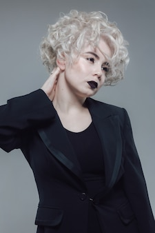巻き毛のブロンドの髪と黒い口紅を持つかなり白人の若い女の子の肖像画