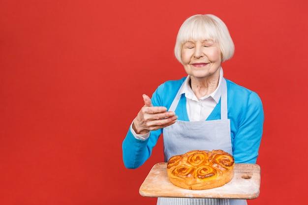 Портрет довольно очаровательной веселой старшей пожилой женщины с морщинками, показывая жестами сладкий домашний пирог
