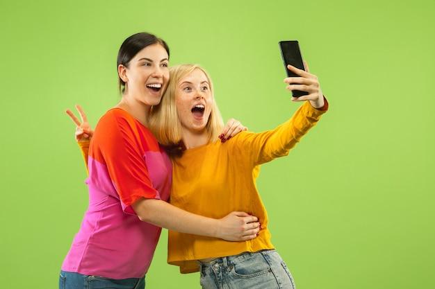 緑のスタジオの背景に分離されたカジュアルな服装でかなり魅力的な女の子の肖像画。自分撮りをするガールフレンドやレズビアン。 lgbtの概念、平等、人間の感情、愛、関係。