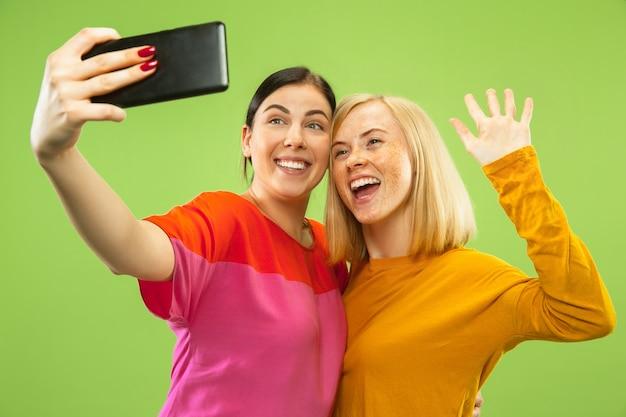 Портрет довольно очаровательных девушек в повседневных нарядах, изолированных на зеленом фоне студии. подруги или лесбиянки делают селфи. понятие лгбт, равенство, человеческие эмоции, любовь, отношения.