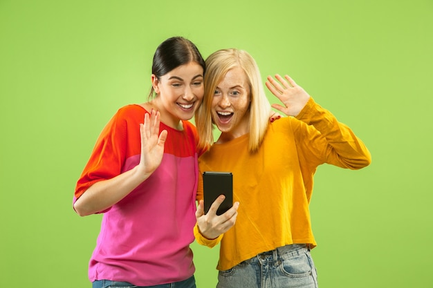 Портрет довольно очаровательных девушек в повседневных нарядах, изолированных на зеленом фоне студии. подруги или лесбиянки разговаривают по смартфону. понятие лгбт, равенство, человеческие эмоции, любовь, отношения.