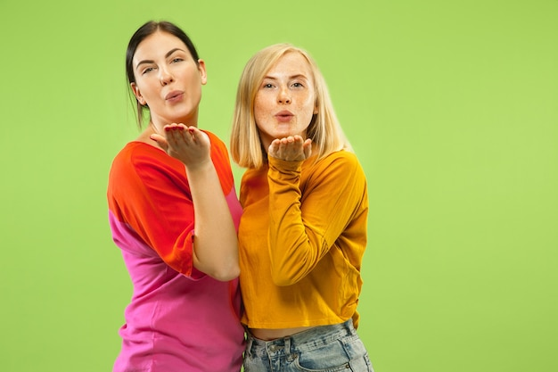 緑のスタジオの背景に分離されたカジュアルな服装でかなり魅力的な女の子の肖像画。ガールフレンドまたはレズビアンとしての2人の女性モデル。 lgbtの概念、平等、人間の感情、愛、関係。