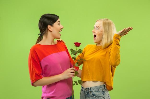 Портрет довольно очаровательных девушек в повседневных нарядах, изолированных на зеленом фоне студии. две девушки-модели в роли подружек или лесбиянок. понятие лгбт, равенство, человеческие эмоции, любовь, отношения.