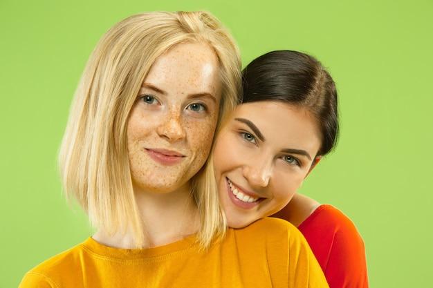 녹색 스튜디오 배경에 고립 된 캐주얼 복장에 꽤 매력적인 여자의 초상화. 여자 친구 또는 레즈비언으로 두 명의 여성 모델. lgbt, 평등, 인간의 감정, 사랑, 관계의 개념.