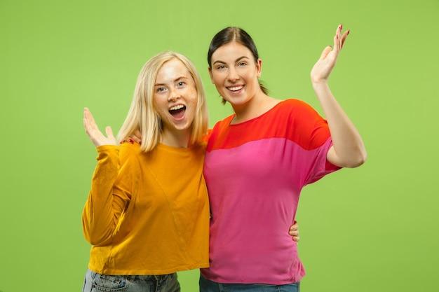 Портрет довольно очаровательных девушек в повседневных нарядах, изолированных на зеленой стене студии