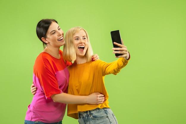 緑の壁に隔離されたカジュアルな服装でかなり魅力的な女の子の肖像画。自分撮りをするガールフレンドやレズビアン。 lgbtの概念、平等、人間の感情、愛、関係。