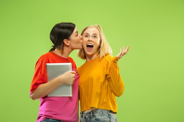 緑の壁に隔離されたカジュアルな服装でかなり魅力的な女の子の肖像画。楽しみや支払いのためにタブレットを使用しているガールフレンドやレズビアン。 lgbtの概念、人間の感情、愛、関係。