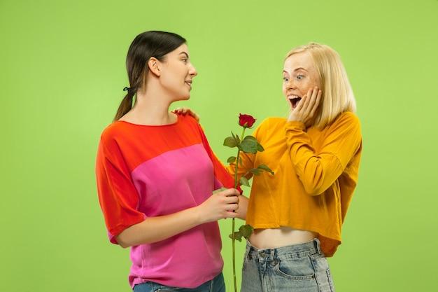 緑の壁に隔離されたカジュアルな服装でかなり魅力的な女の子の肖像画。ガールフレンドまたはレズビアンとしての2人の女性モデル。 lgbtの概念、平等、人間の感情、愛、関係。