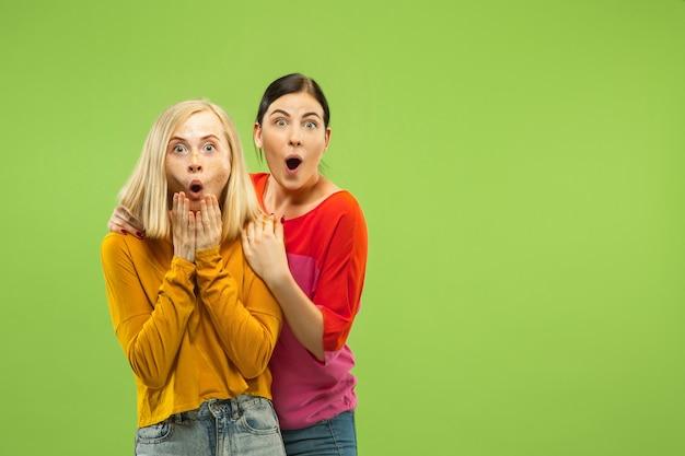 Портрет довольно очаровательных девушек в повседневных нарядах на зеленой студии