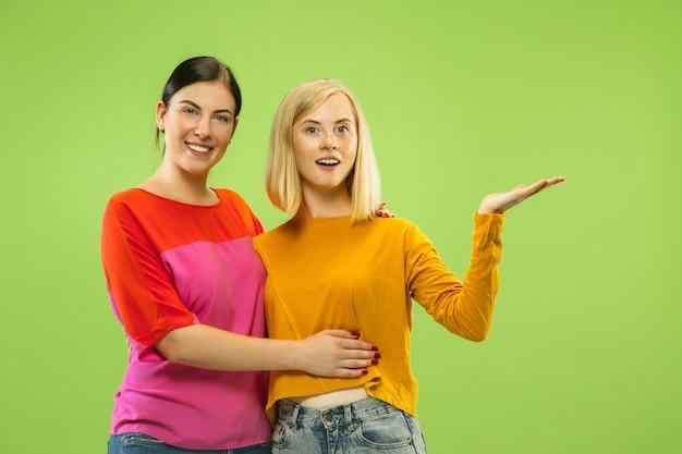 緑のスタジオでカジュアルな服装でかなり魅力的な女の子の肖像画