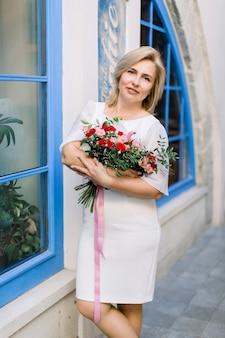 エレガントな白いドレスを着て、花の花束を持って、大きな青い窓のある街のヴィンテージの建物の近くでポーズをとって、かなり魅力的な快適な40歳の金髪の女性の肖像画