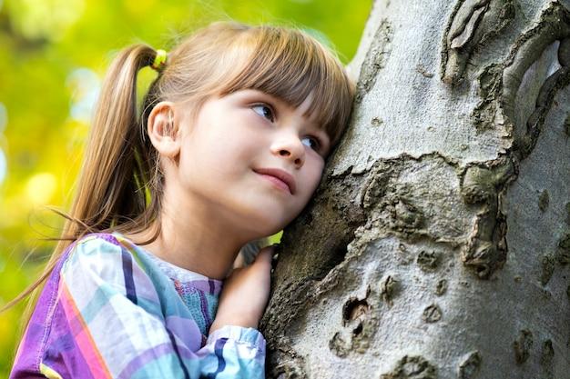 秋の公園でリラックスした木の幹にもたれてかわいい子少女の肖像画。森の暖かい秋の天気を楽しんでいるかわいい女性の子供。