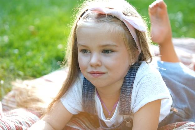 Портрет девушки довольно ребенка, отдыхая на открытом воздухе в летнем парке.