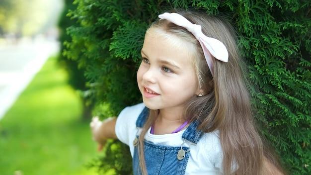 緑の夏の公園で屋外に立っているかわいい子の女の子の肖像画。