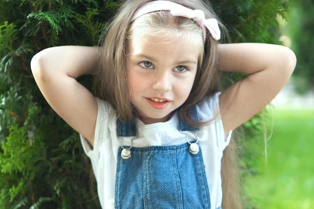 행복 하 게 웃 고 여름 공원에 야외에서 서 있는 예쁜 아이 소녀의 초상화.