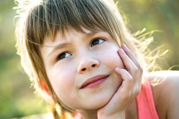 Портрет довольно ребенка девушка с серыми глазами и длинными светлыми волосами, опираясь на руки, счастливо улыбаясь на открытом воздухе на размытом ярком фоне