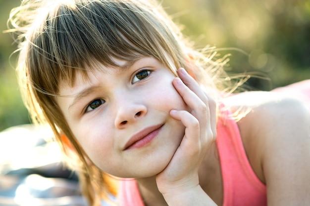 Портрет красивой девочки с серыми глазами и длинными светлыми волосами, опираясь на руки, счастливо улыбаясь на открытом воздухе на размытой яркой поверхности