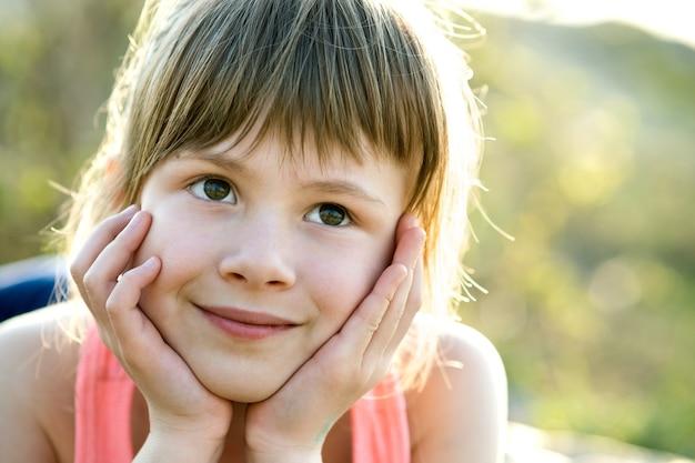 회색 눈과 긴 공정한 머리가 그녀의 손에 기대어 야외에서 행복하게 웃는 예쁜 아이 소녀의 초상화