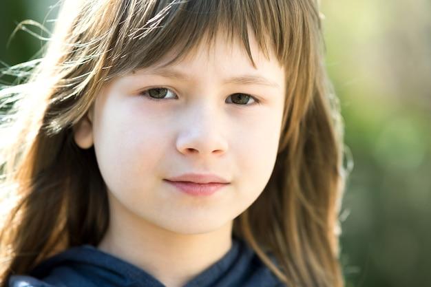 회색 눈과 흐린 밝은 배경에 야외에서 긴 공정한 머리와 예쁜 아이 여자의 초상화. 외부 따뜻한 여름날에 귀여운 여자 꼬마.
