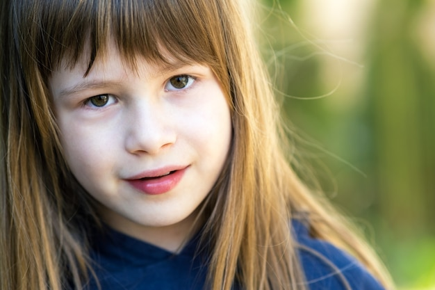 Портрет красивой детской девочки с серыми глазами и длинными светлыми волосами на открытом воздухе на размытой зеленой яркой поверхности