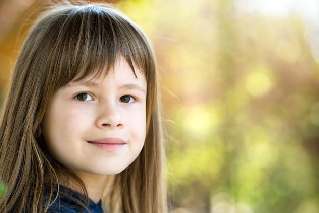 Портрет красивой детской девочки с серыми глазами и длинными светлыми волосами, улыбаясь на открытом воздухе на размытом ярком фоне. милый ребенок женского пола в теплый летний день снаружи.