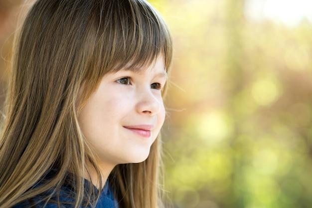 Портрет красивой детской девочки с серыми глазами и длинными светлыми волосами, улыбаясь на открытом воздухе на размытой яркой поверхности