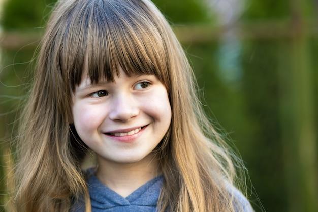 회색 눈과 흐린 녹색 밝은에 야외에서 웃 고 긴 공정한 머리와 예쁜 아이 여자의 초상화