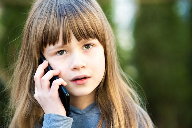 Портрет красивой девушки ребенка с длинными волосами, говорящими по мобильному телефону. маленький ребенок женского пола общается с помощью смартфона. концепция общения детей.
