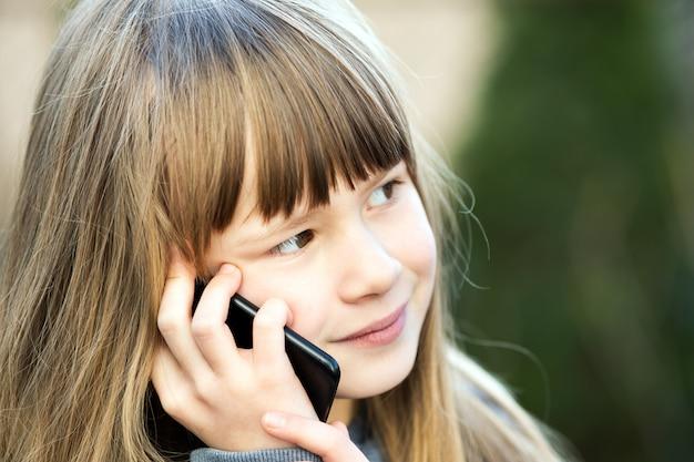 Портрет довольно ребенка девушка с длинными волосами, говорить на мобильный телефон. маленький женский ребенок, общение с помощью смартфона. концепция общения детей.