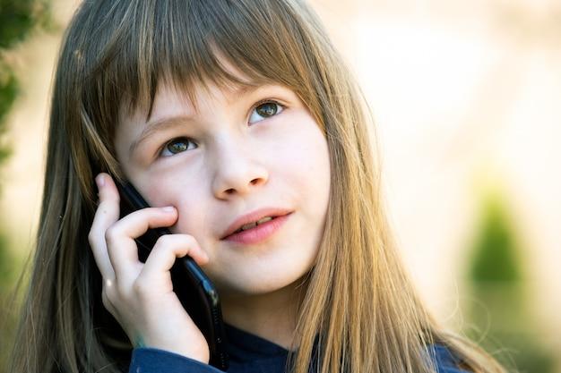 携帯電話で話している長い髪のかわいい子少女の肖像画。スマートフォンを使用して通信する小さな女性の子供。子供のコミュニケーションの概念。