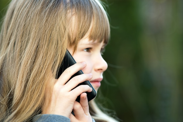 携帯電話で話している長い髪のかわいい子少女の肖像画