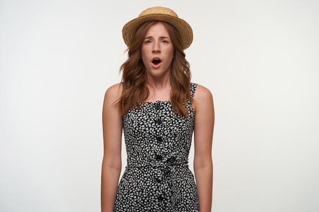 ロマンチックなドレスとカンカン帽の帽子を身に着けて、白い背景の上に立って、開いて眉をひそめているカメラを見て、かなり混乱している若い赤毛の女性の肖像画