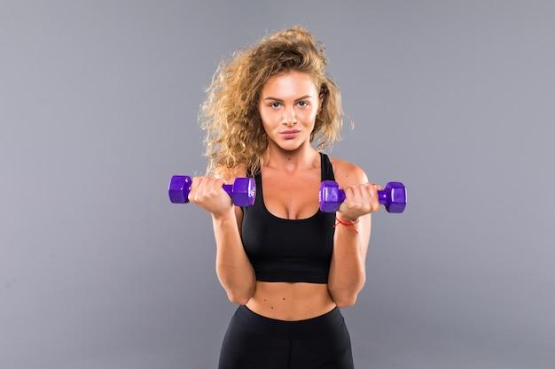 Портрет довольно кудрявой спортивной девушки, держащей гантели с весами, изолированной на серой стене