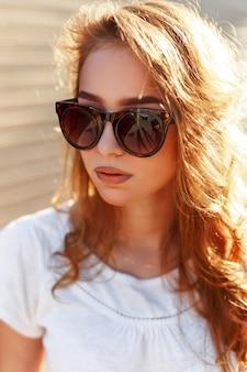 木製の壁を背景にブロンドの髪と白い夏のスタイリッシュなtシャツの流行のサングラスでかわいい流行に敏感な若い女性の肖像画