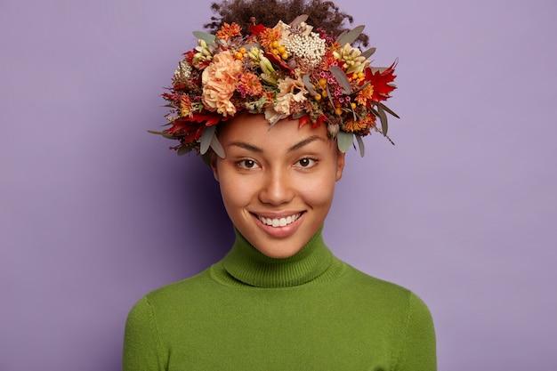 꽤 어두운 피부를 가진 여성의 초상화가 즐겁게 미소 짓고 가을 꽃으로 만든 화환을 착용합니다.