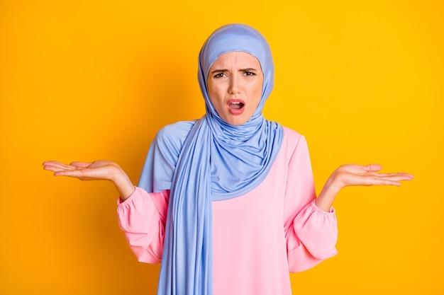 밝은 노란색 배경에 격리된 히잡을 쓴 무관심한 오해의 표현을 쓴 필사적인 이슬람교도 초상화