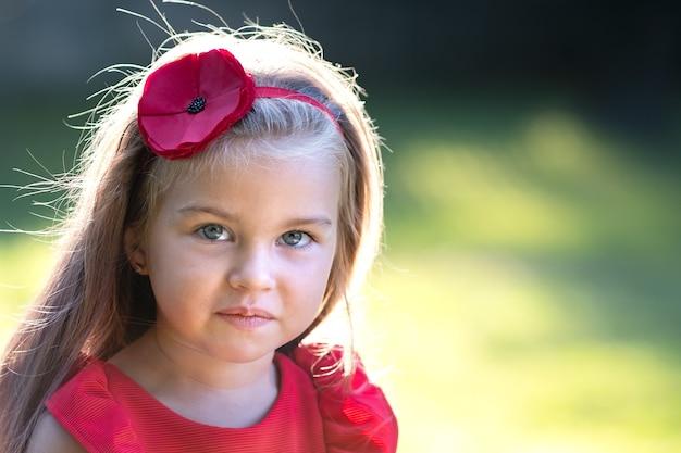 따뜻하고 화창한 여름 날을 즐기는 빨간 드레스에 꽤 유행 아이 소녀의 초상화.