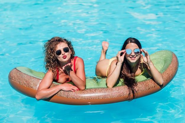 海の膨脹可能なおもちゃのキウイの上に横たわっているビキニを着ているきれいな女性の友人の肖像画。フローティングプールの膨脹可能なおもちゃで日光浴をしている女性。