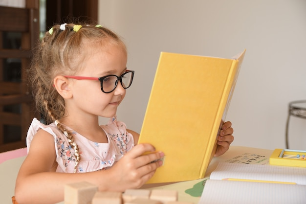 教科書を読みながら教室に座っているきれいな女性の幼稚園の学生の肖像画。