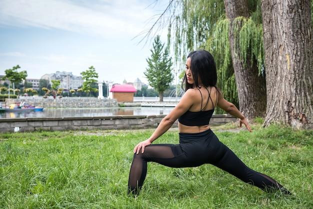 Портрет красивой женщины фитнеса в спортивной одежде, делая упражнения на растяжку на открытом воздухе. спорт для здоровья