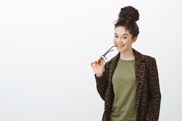 Портрет довольно кокетливой студентки брюнетки с вьющимися волосами, кусающей оправой очков и улыбающейся